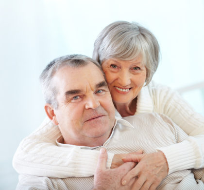 Happy portrait of senior couple, woman embracing her husband